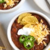 Two white bowls filled with slow cooker turkey chili garnished with cheese sour cream jalapenos and tortilla chips