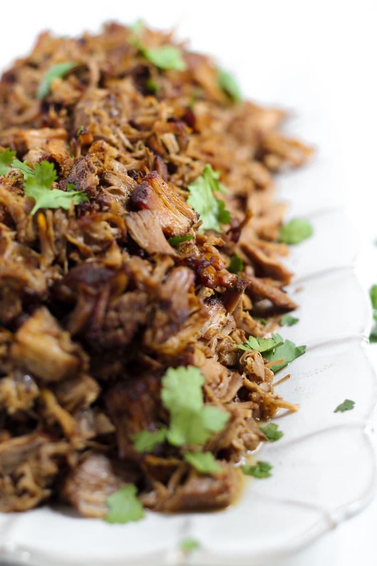 Platter of shredded pork carnitas garnished with fresh chopped cilantro