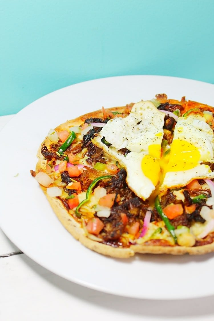 BBQ Pork Carnitas Breakfast Pizza loaded with veggies, pico de gallo and a fried egg.