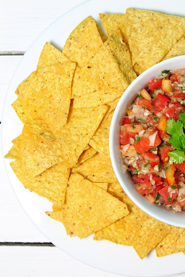 A white bowl filled with homemade salsa loaded with tomato onion garlic and cilantro