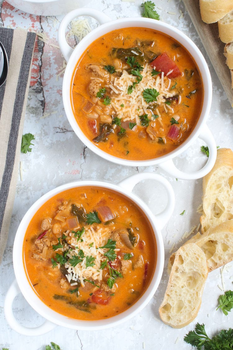 Spicy sausage soup with tomatoes and white beans garnished with Parmesan and parsley