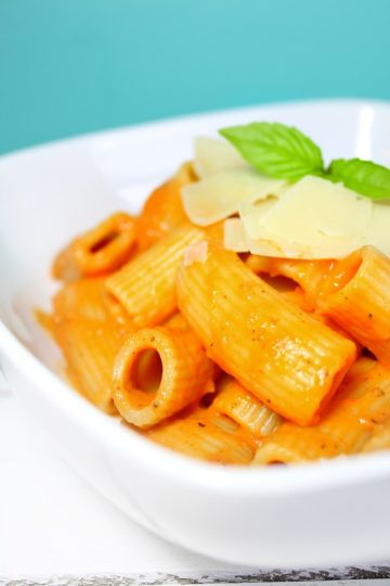 A big while bowl filled with rigaotni tossed in homemade roasted tomato cream sauce garnished with fresh basil and parmesan cheese