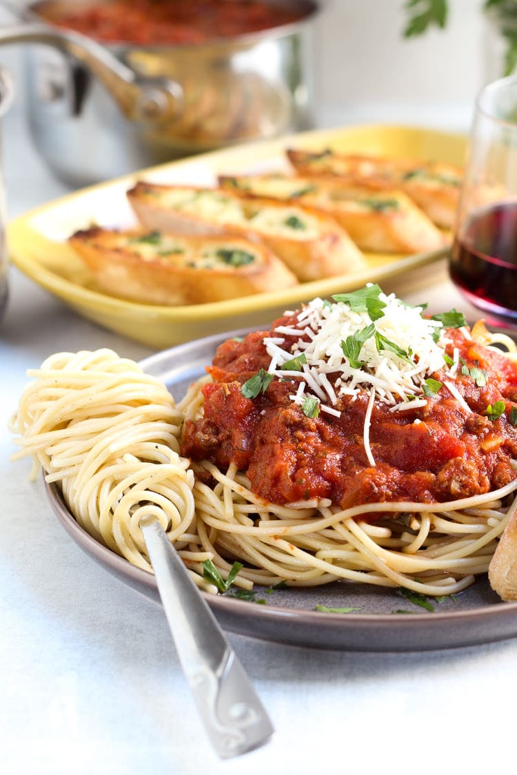 A plate full of spaghetti noodles with homemade spaghetti sauce garnished with Parmesan cheese and fresh parsley