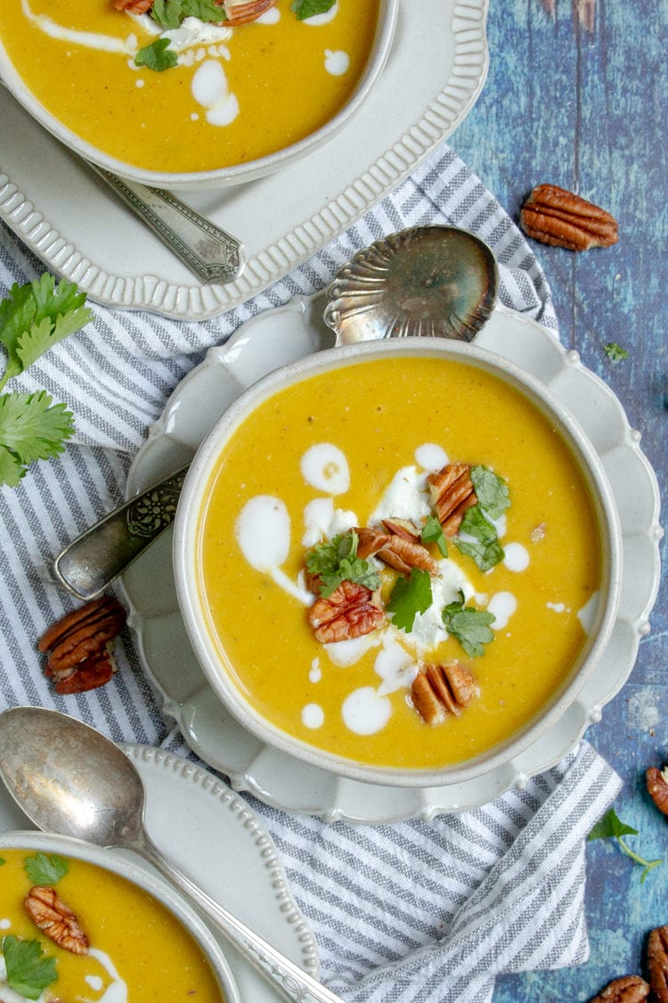 Three bowls of curried squash soup garnished with coconut milk cilantro and pecans