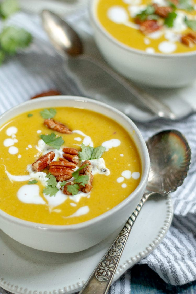 Two bowls of curried squash soup garnished with coconut milk cilantro and pecans