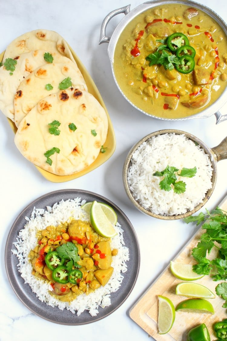 Large curry vegan slow curry spread complete with curry rice naan cilantro and lime wedges