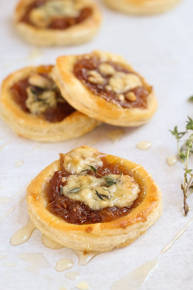 Caramelized onion and blue cheese puff pastry tarts garnished with a drizzle of honey and fresh thyme leaves