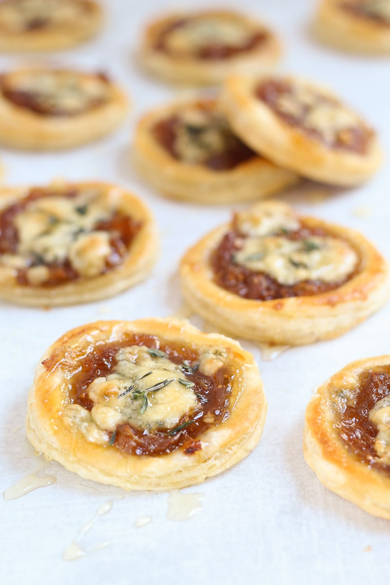 Caramelized onion and blue cheese puff pastry tarts garnished with a drizzle of honey and sprinkled with fresh thyme