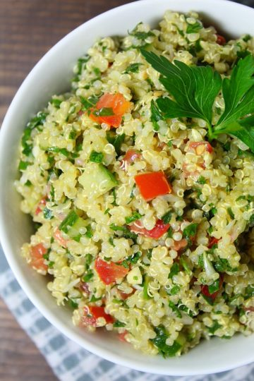 Large white serving bowl filled with homemade tabbouleh garnished with fresh parsley