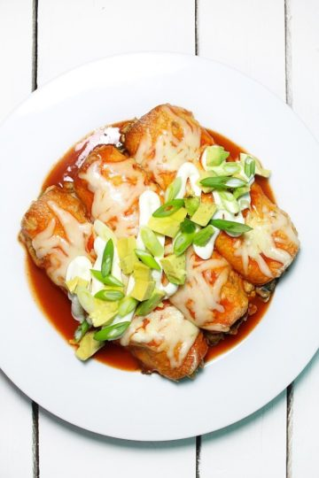 White serving latter with loaded vegetarian enchiladas garnished with sour cream and diced avocado