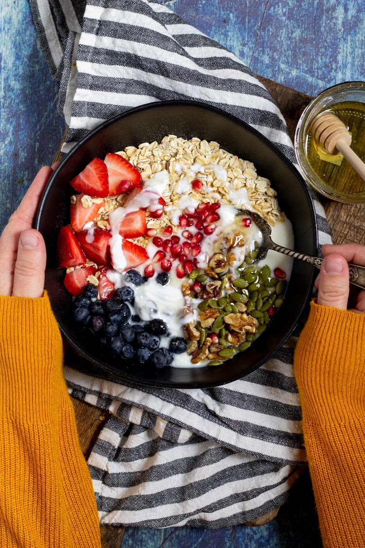 A large black bowl filled with oatmeal fruit and yogurt on a table with a spoon digging in ready to take a bite