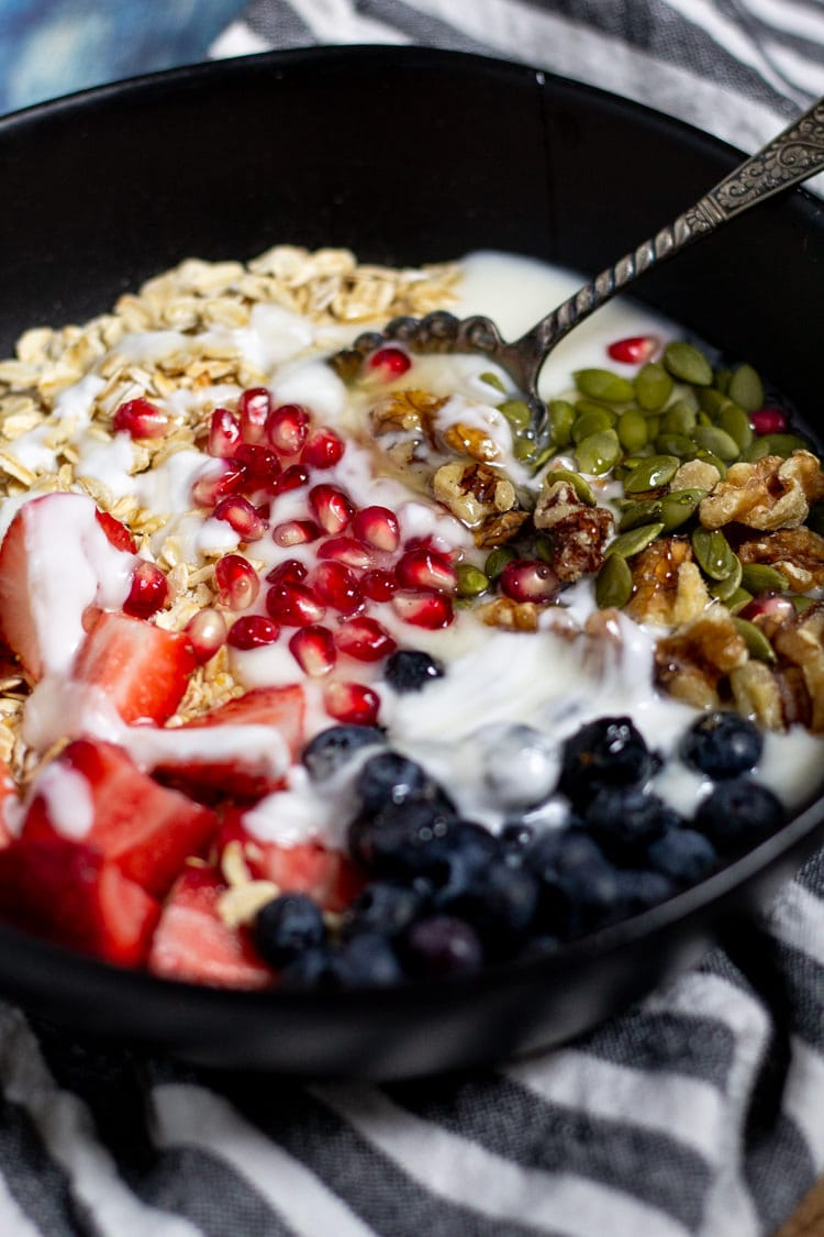 Large black bowl filled with a hearty breakfast of oats along with yogurt fruit and nuts