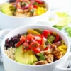 Three bowls filled with grilled chicken veggies corn beans avocado and pico de gallo