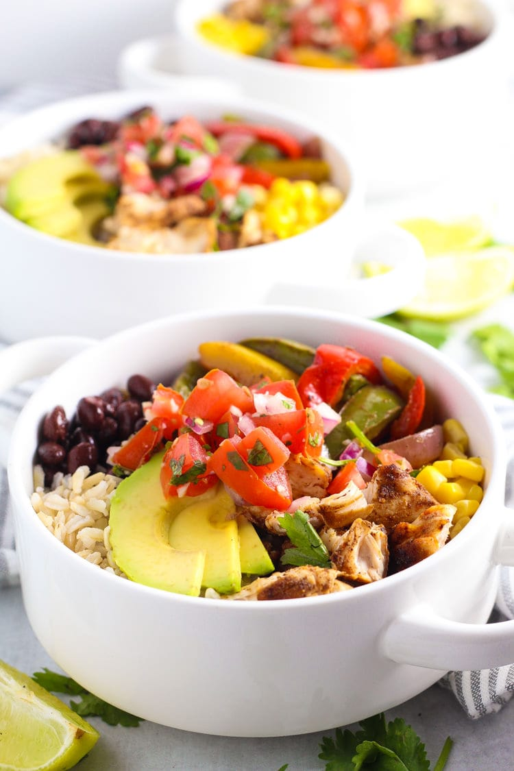 Chicken fajita meal prep bowls loaded with rice veggies corn beans avocado and pico de gallo