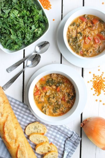 Two bowls of hearty sausage lentil soup with kale served with sliced French baguette
