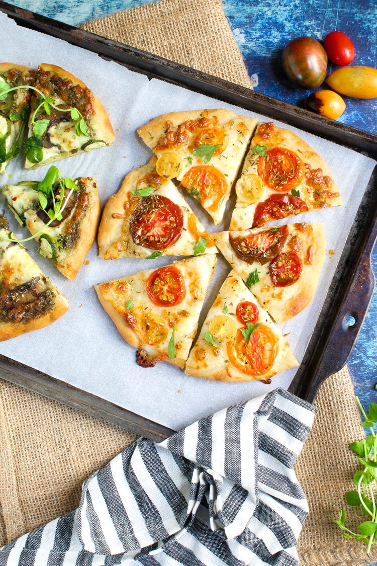 Two mini pizza topped with fresh seasonal ingredients baked up golden brown and crispy