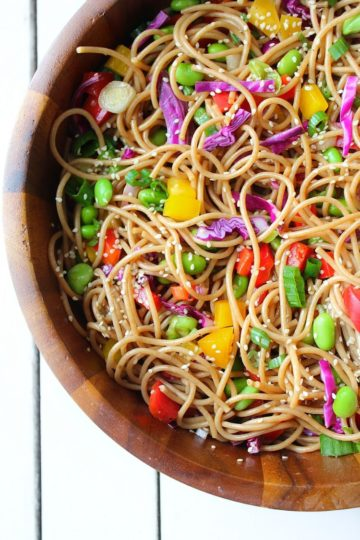 Large wooden bowl filled with freshly tossed sesame ginger pasta salad loaded with veggies
