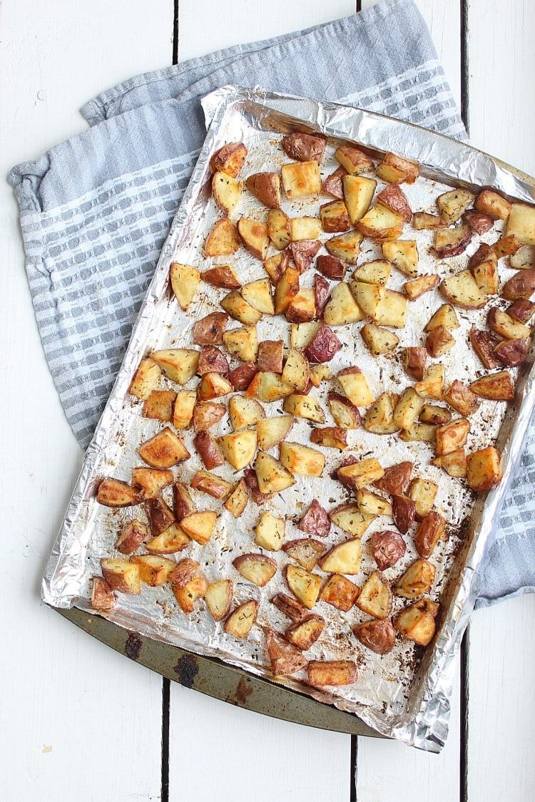 A sheet pan filled with freshly roasted breakfast potatoes on a blue checkered towel on a white wooden tables