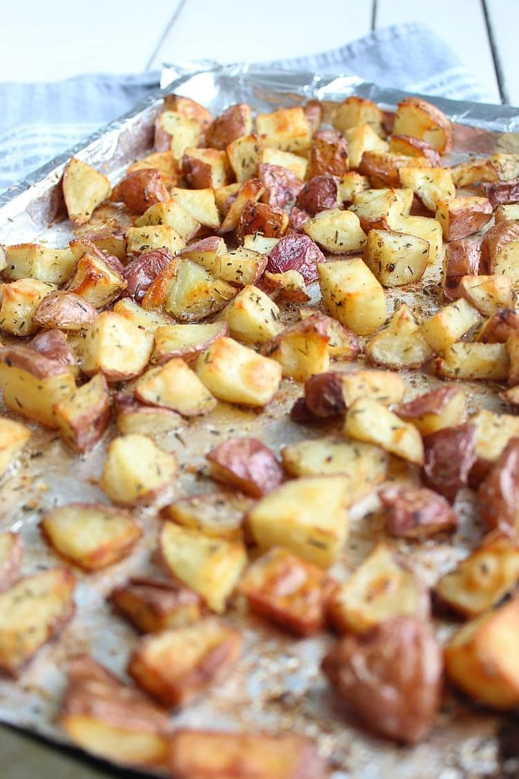 A sheet pan filled with freshly roasted diced breakfast potatoes