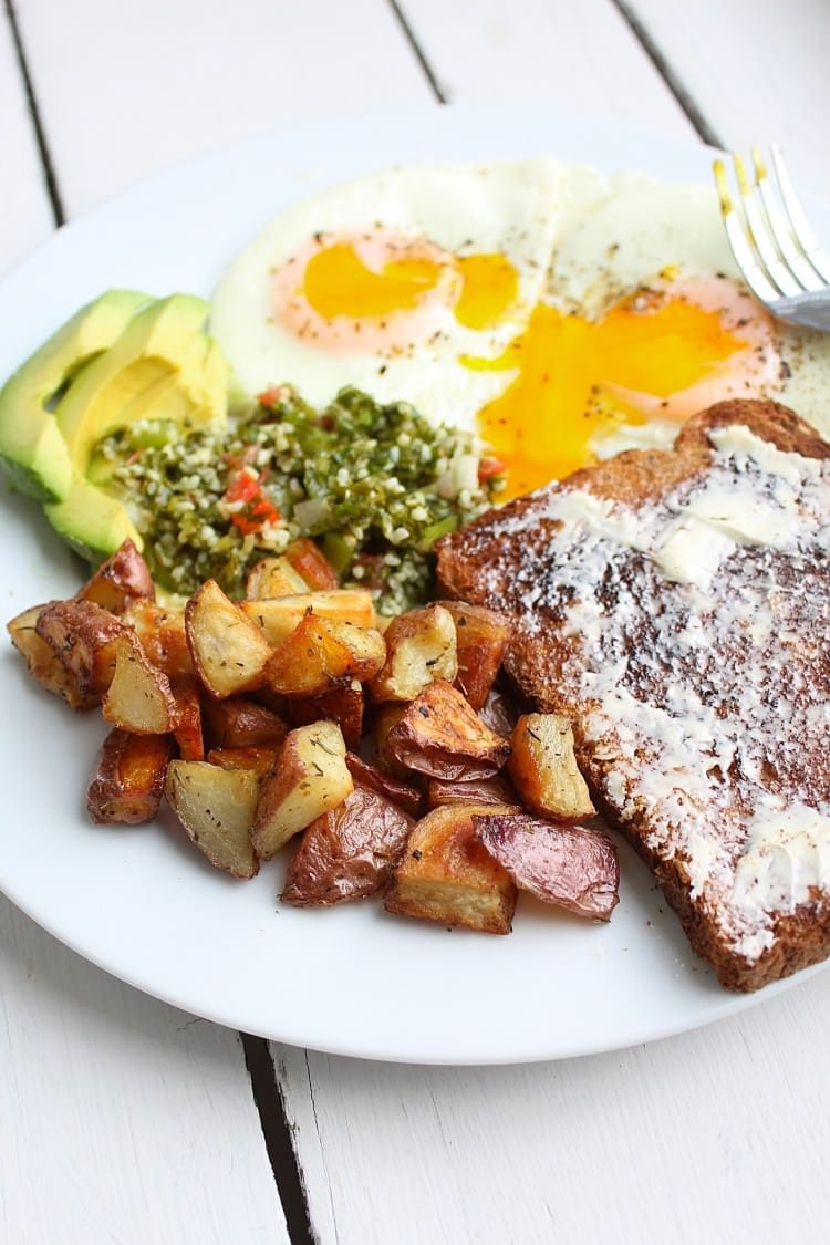 White plate filled with potatoes eggs toast and avocados