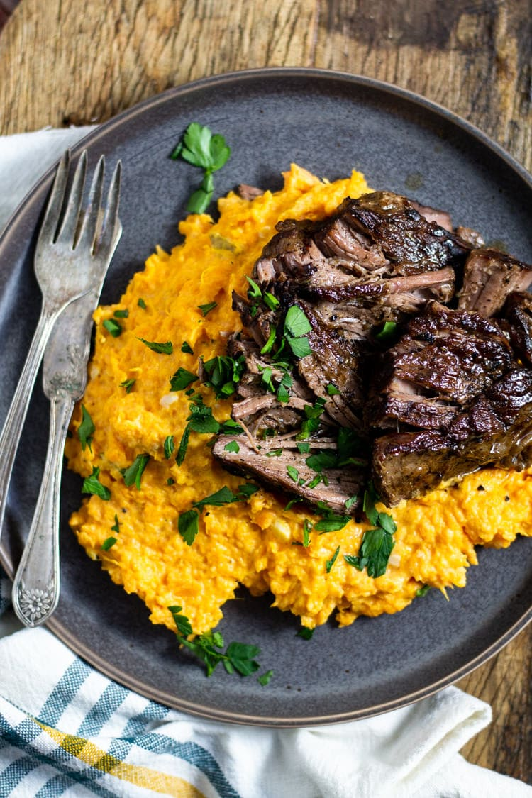Large plate with garlic mashed sweet potatoes and bourbon braised beef garnished with fresh chopped parsley