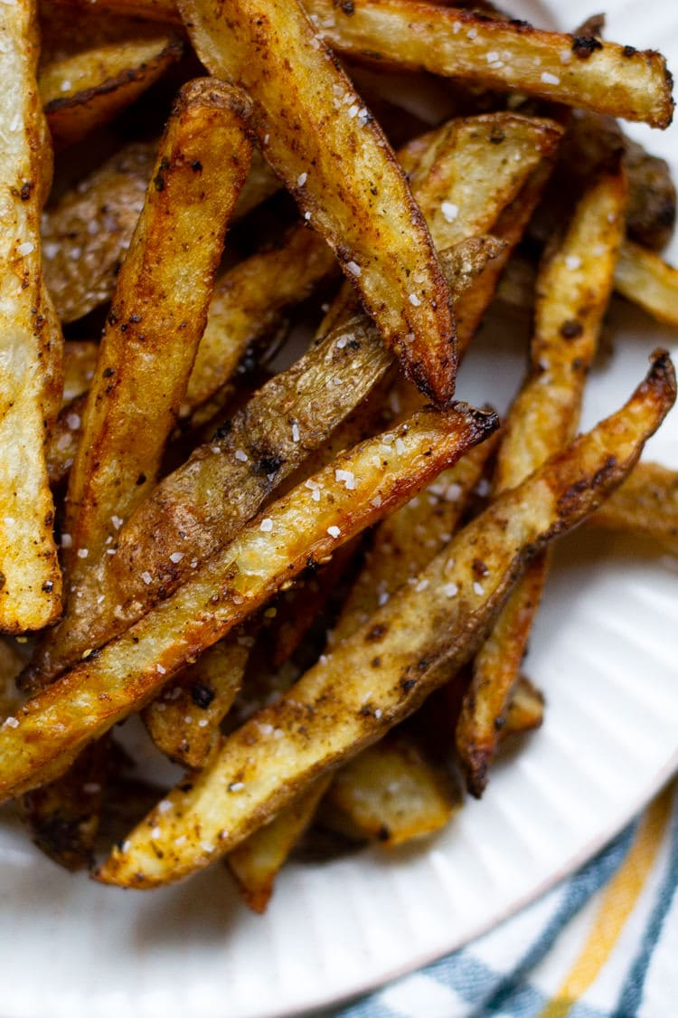 A white plate filled with baked fries