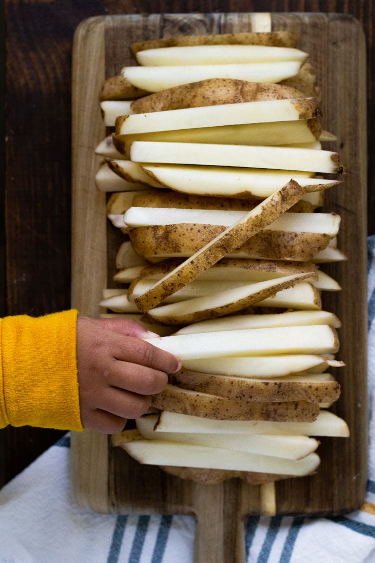 A cutting board filled with potatoes cut into fries with a little hand grabbing one fry