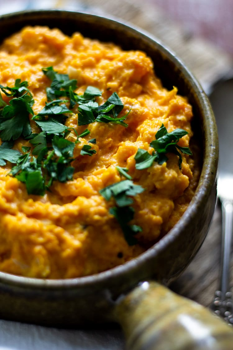 Green ceramic bowl of garlic mashed sweet potatoes garnished with fresh chopped parsley