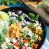 A black bowl loaded with a southwest salad filled with veggies and drizzled with homemade dressing