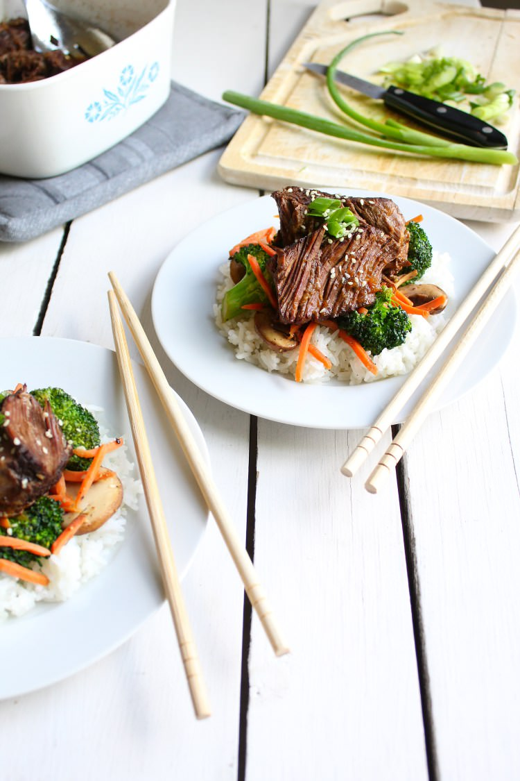 Two white plates filled with white rice sauteed veggies and tender slow cooker Asian beef