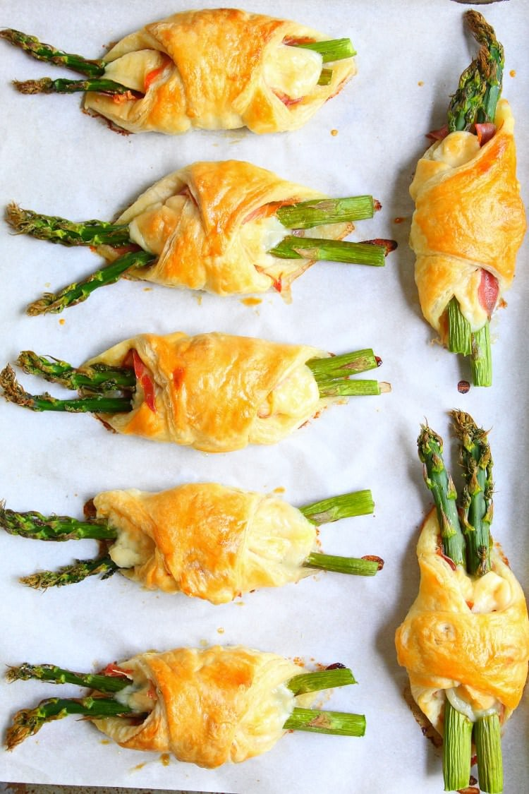 Parmesan proscuitto and asparagus bundles fresh baked from the oven resting on a parchment lined sheet pan