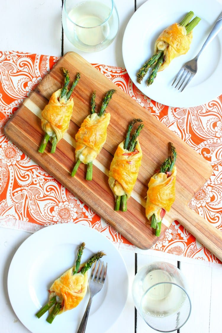 Parmesan proscuitto and asparagus bundles on a wooden serving platter on table with two plates of bundles and two glasses of white wine
