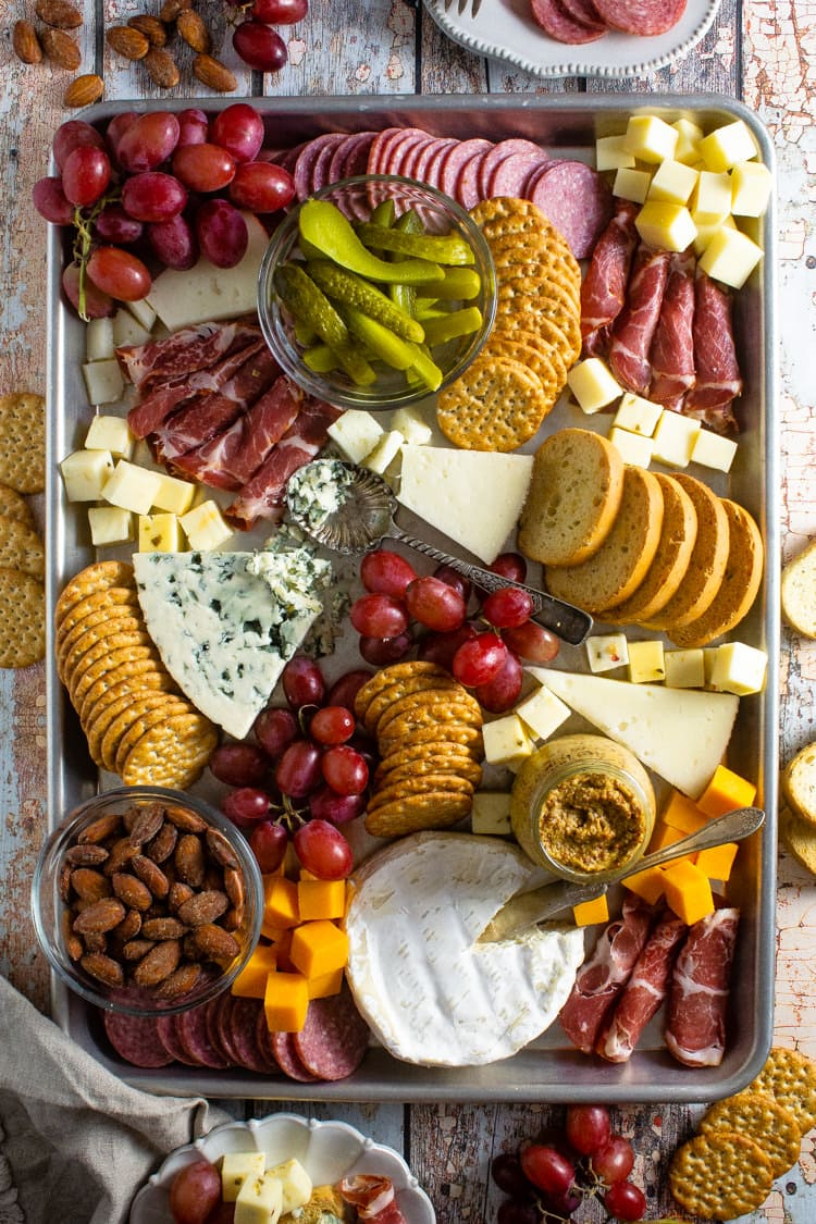 Baking sheet filled with a variety of cheeses meats crackers and grapes