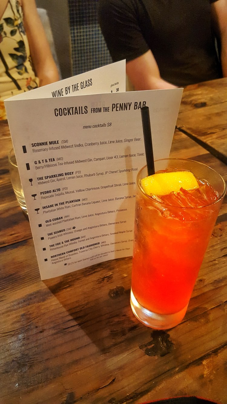 A close up photo of a specialty cocktail on a wooden table at the informalist