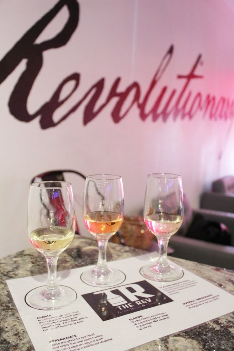 Three wine glasses on top of the tasting menu on the wine tasting counter