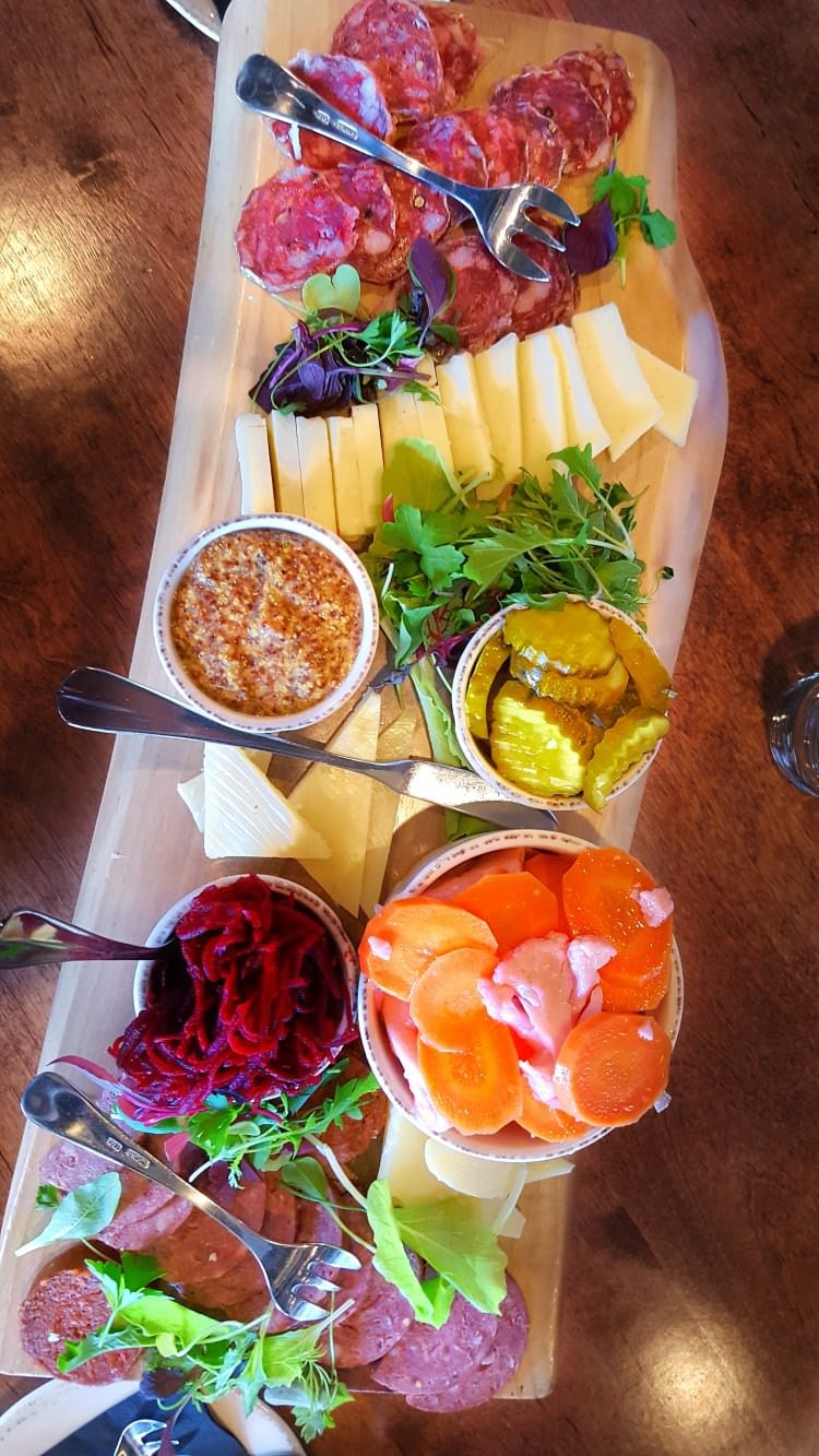 A freshly prepared cheese board loaded with meats veggies and cheeses