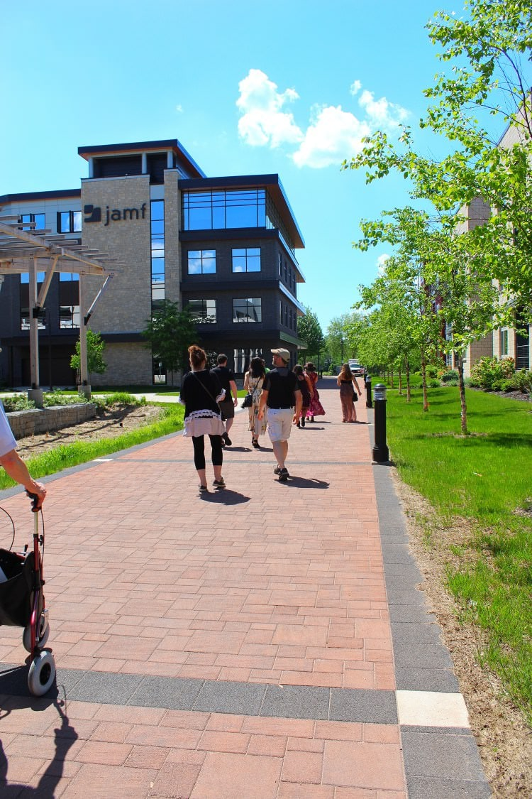 A group of tour goers walking through a local downtown park on a sunny day with blue skies