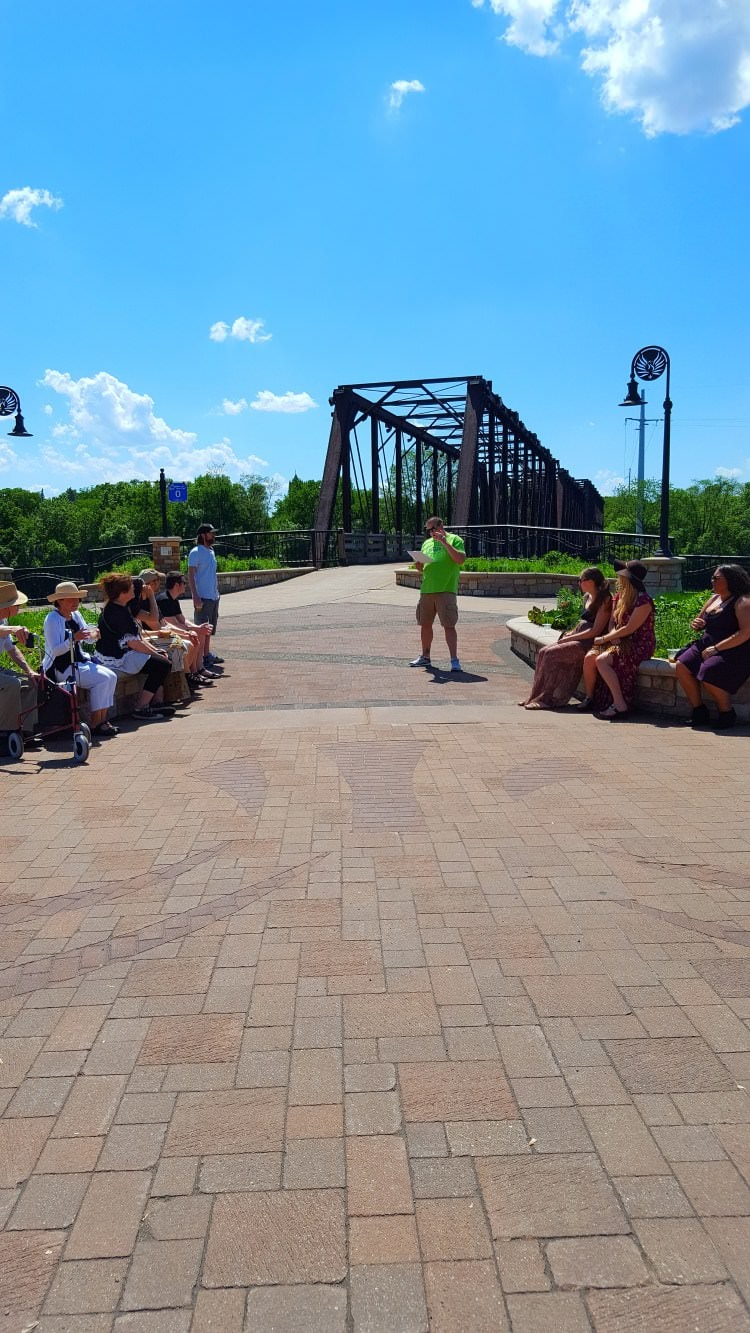 A group of tour goers relaxing in a downtown park near a river