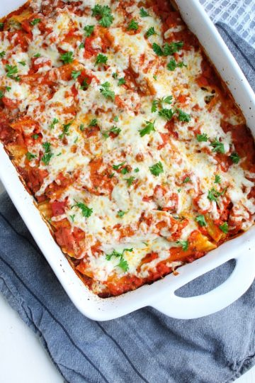 A white baking dish filled with baked manicotti garnished with fresh chopped parsley