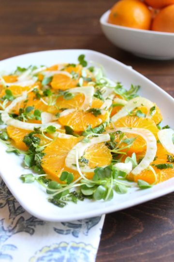Large white serving platter filled with orange fennel salad with mint vinaigrette garnished with micro greens