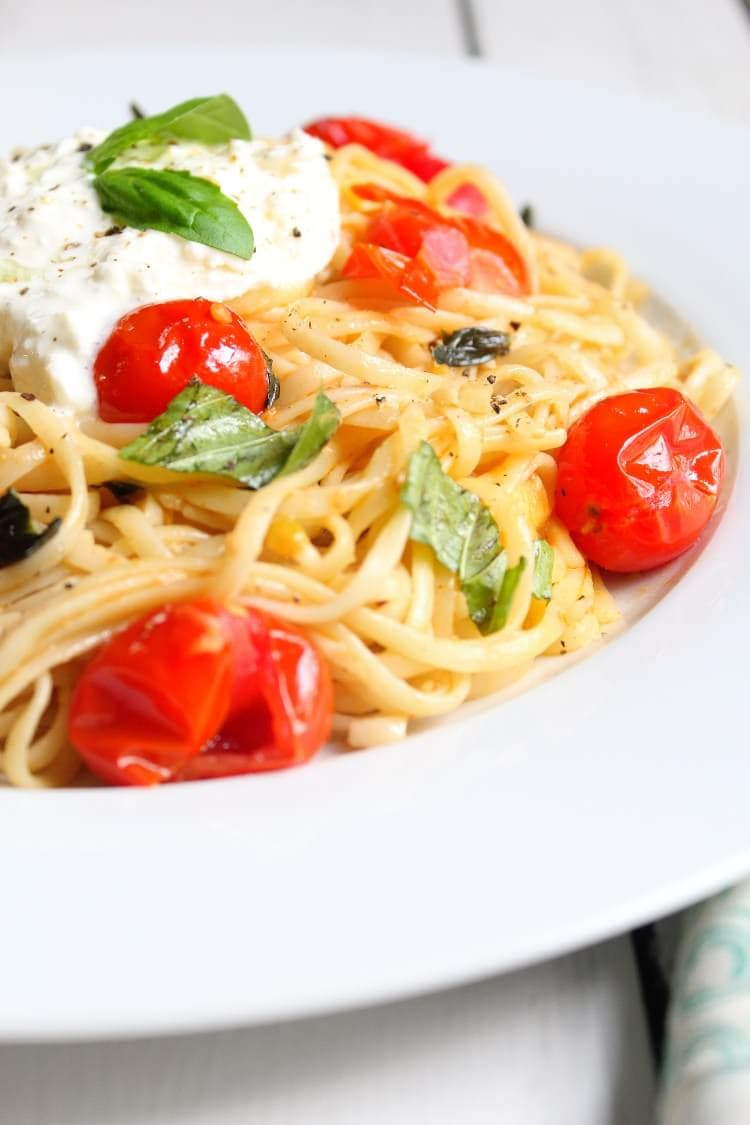 A white plate loaded with tomato basil linguine with fresh burrata and black pepper