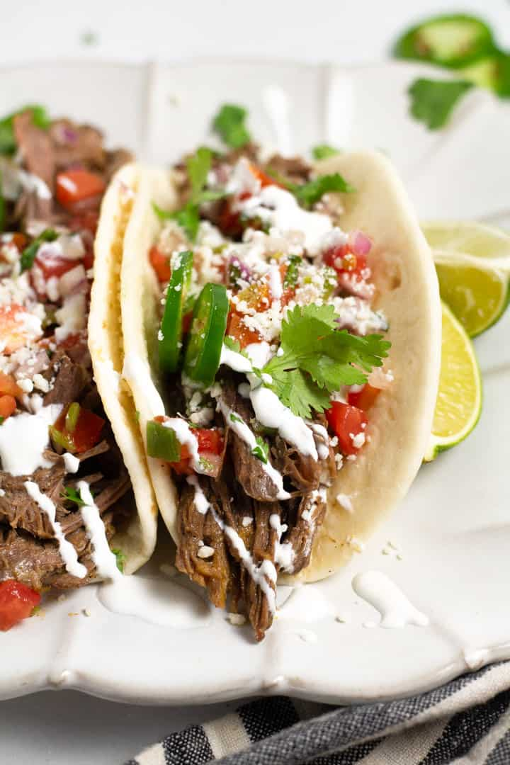 Close up shot of a barbacoa beef platter garnished with fresh cilantro and sour cream