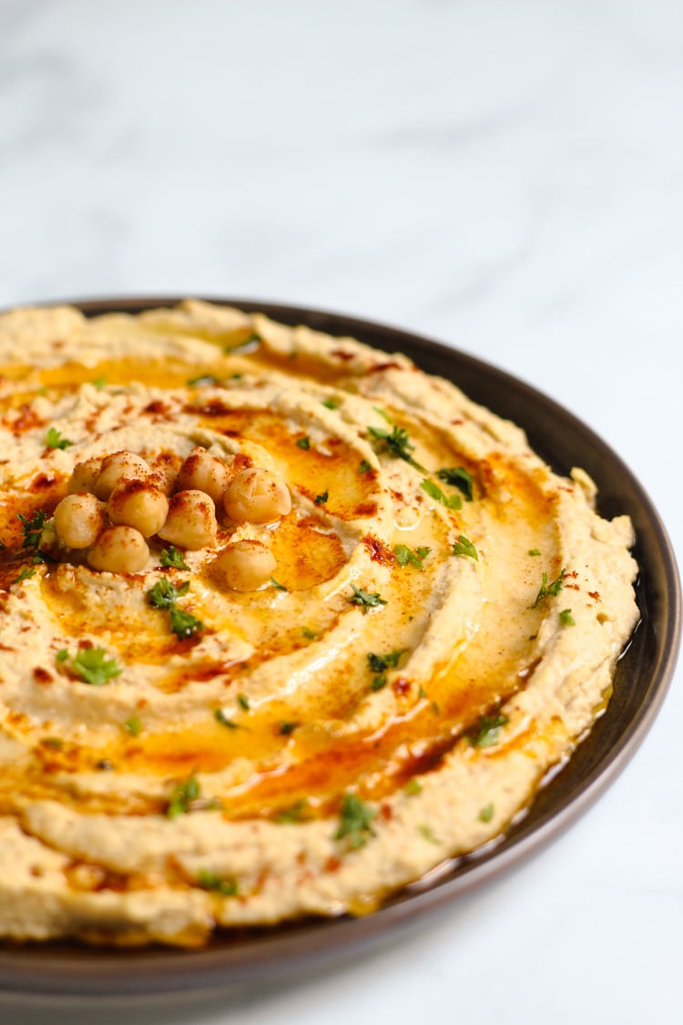 Small serving platter of homemade garlic hummus garnished with olive oil parsley and paprika