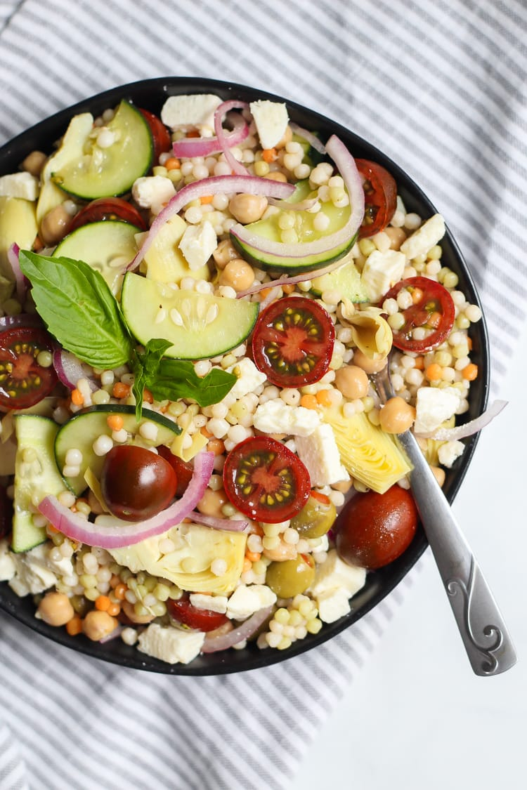 Big bowl of Mediterranean couscous salad loaded with fresh vegetables and feta cheese