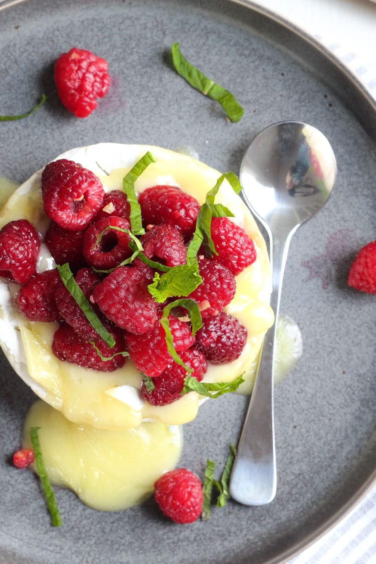A wheel of baked camembert cheese with rose soaked raspberries garnished with fresh mint