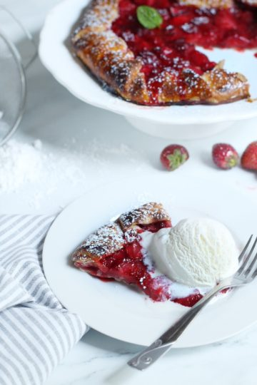 A slice of strawberry galette topped with a big scoop of vanilla ice cream