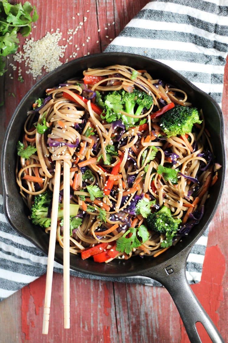 Cast iron skilled filled with veggie lo mein twirled around two wooden chopsticks