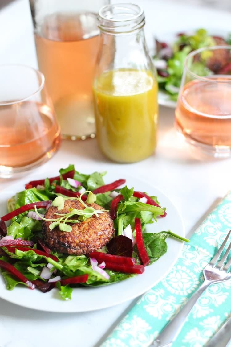 White plate filled with pecan crusted goat cheese salad with julienne roasted beets served with wine and a bottle of dressing