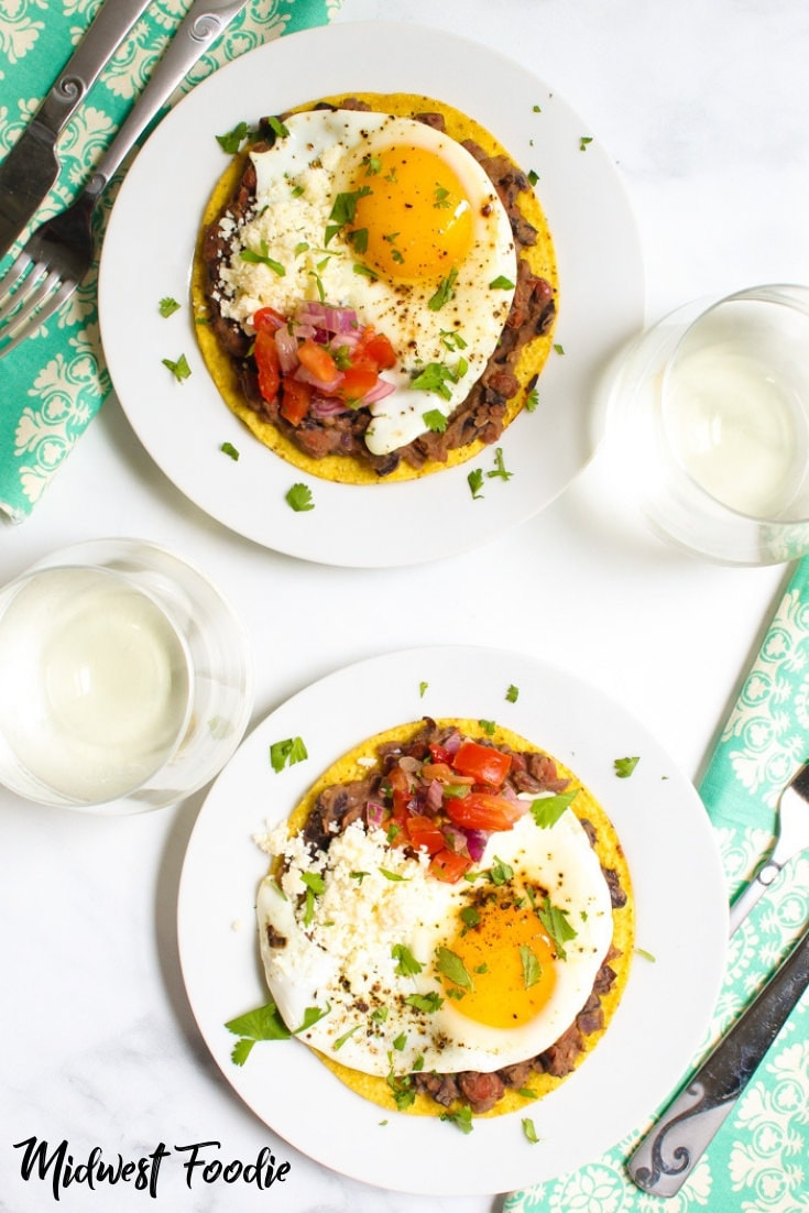 Vegetarian Brunch Tostadas -- Layer tostadas with beans, fry a couple eggs and garnish with cotija cheese and pico de gallo and you're brunching like a rockstar! Fresh flavors combined with healthy, satisfying, whole ingredients transform your boring breakfast into a memorable brunch experience! #midwestfoodie #healthy #easy #simple #eggs #tostadas #Mexican #vegetarian #fitfamily #familydinner