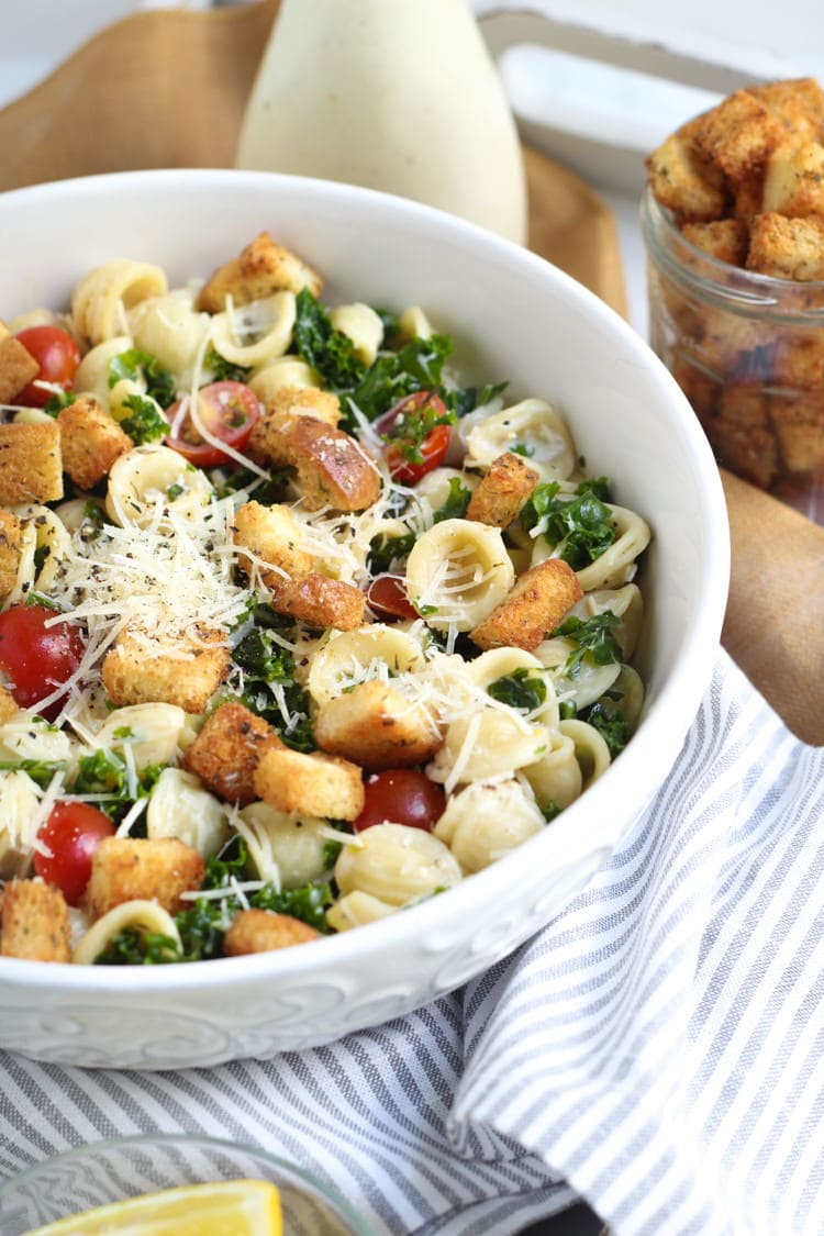 White bowl filled with kale caesar salad loaded with croutons Parmesan cheese and tomatoes